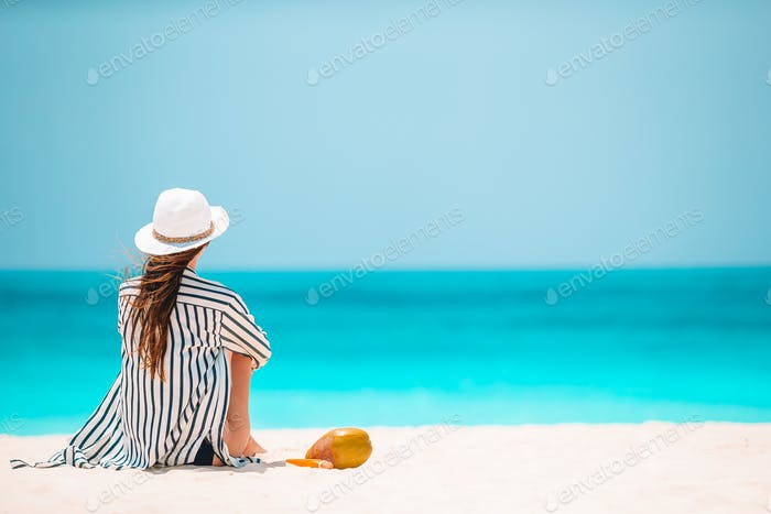 Young woman on white beach with coconut