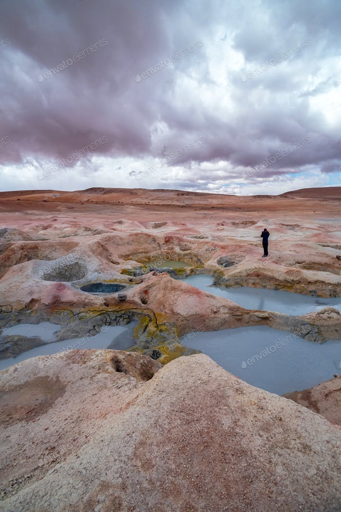 Woman with a camera photographing some mud pits with volcanic activity in the Andean Highlands