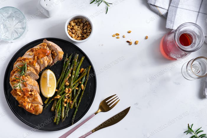Grilled chicken breast with grilled asparagus and lemon slice on stone. Paleo diet. Concept for a