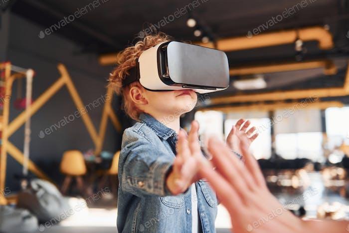Niño en gafas de realidad virtual y en ropa casual divertirse en la sala de juegos