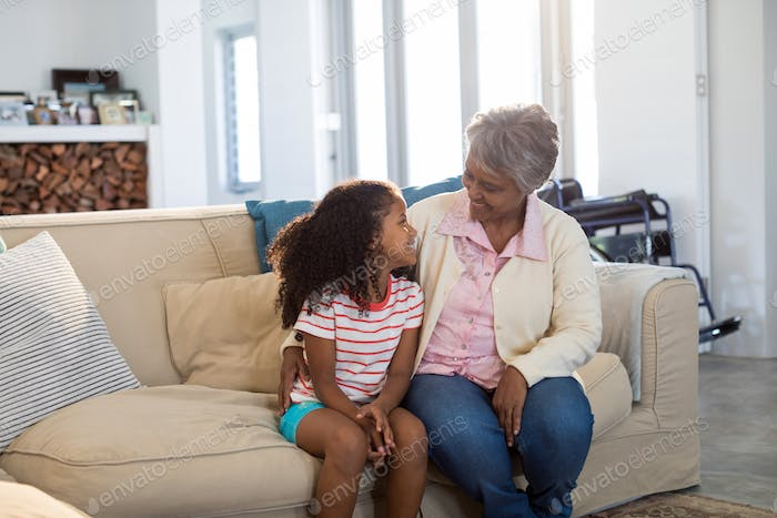 Smiling grandmother interacting with granddaughter in living room