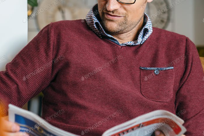 Crop young man reading article in newspaper