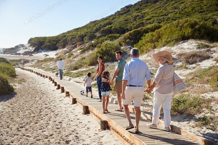Drei Generationen weiße Familie zusammen entlang einer hölzernen Promenade an einem Strand, voller Länge