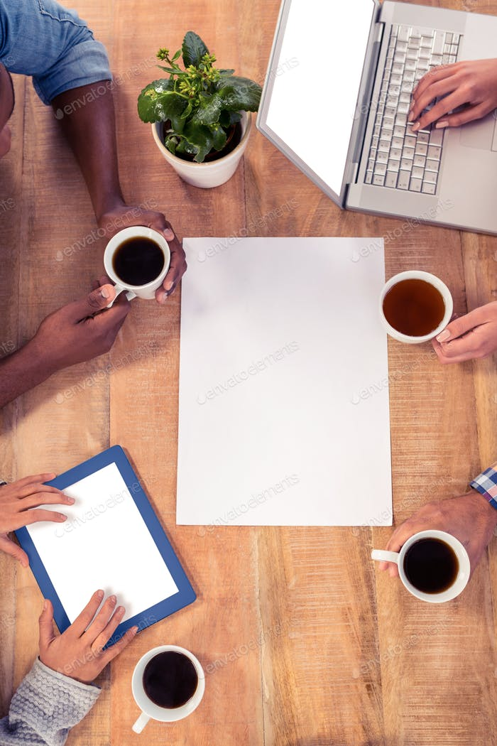 Business people using technologies while holding coffee cups at desk