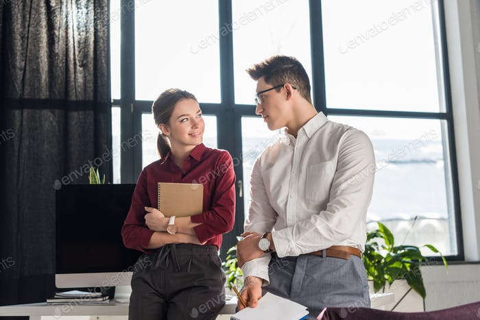 attractive young manageress flirting with her colleague, office romance concept