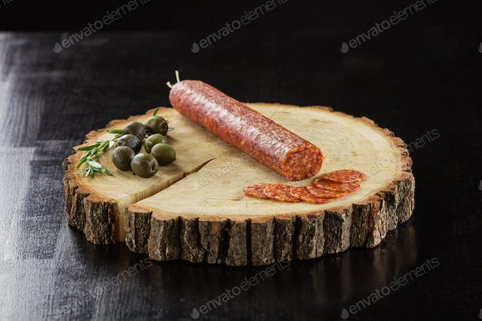 Smoked sausage and olives over black