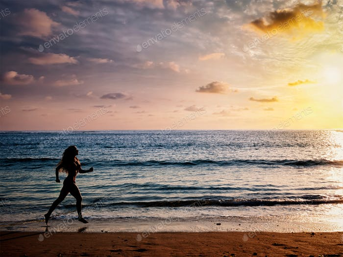 Beautiful athletic woman running along sea beach in the morning