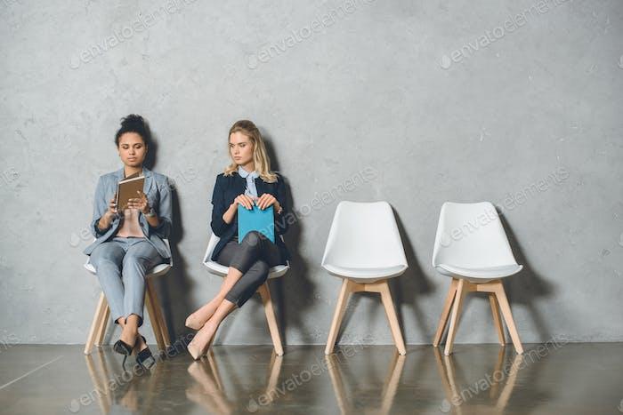 молодые мультикультурные предпринимательницы сидят на стульях и ждут собеседования
