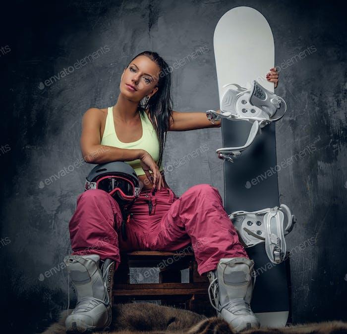 Eine Frau posiert mit Snowboard in einem Studio.