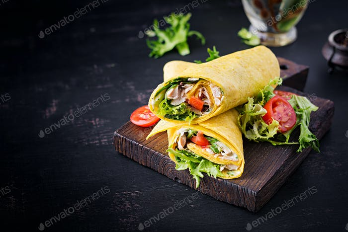 Fresh tortilla wraps with chicken and fresh vegetables on wooden board.