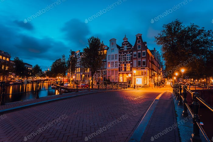 Amsterdam illuminated bridge with typical dutch houses in evening blue hour lights, Holland