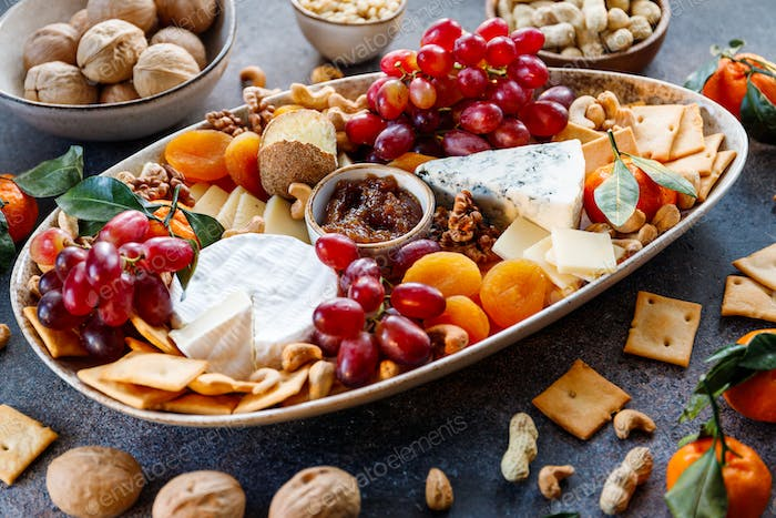 Big plate with appetizer assortment. Grape, cheese, nuts, jam and bread.