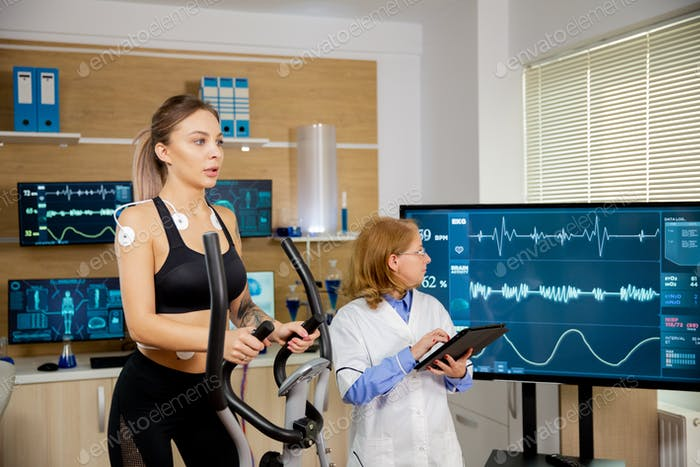 Fit female testing the stepper with electrodes on it and the doctor watching the evolution of the