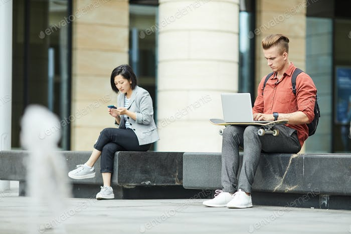 Young People Using Electronic Devices in City