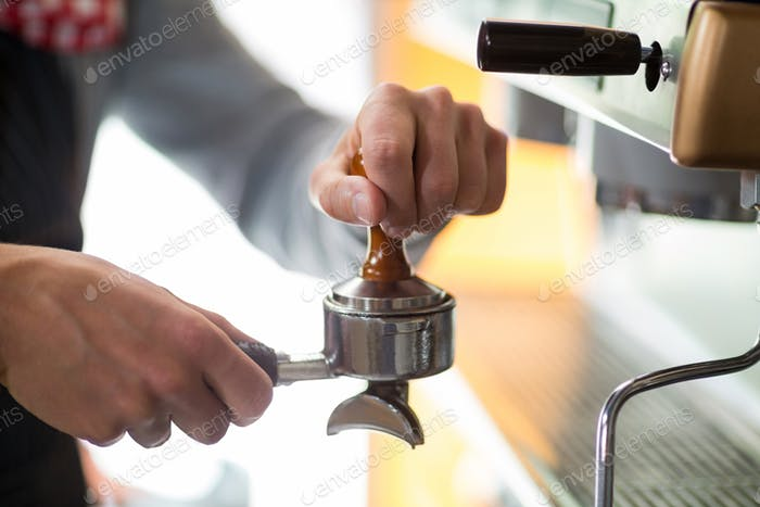 Waiter using a tamper to press ground coffee into a portafilter
