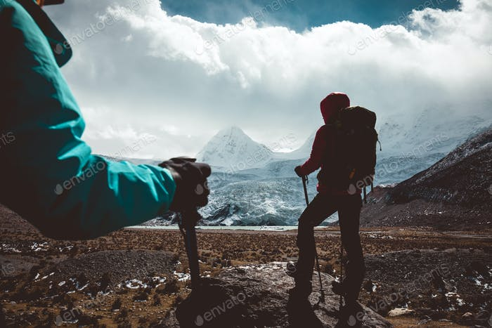 Two women hikers hiking in winter high altitude mountains