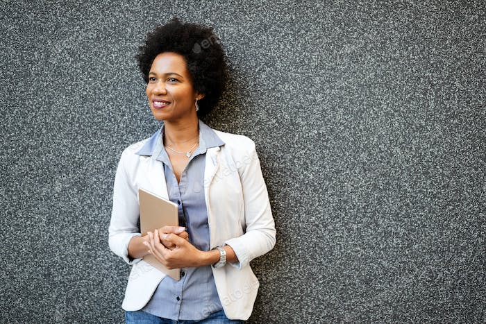 Happy businesswoman with digital tablet outdoor over building background