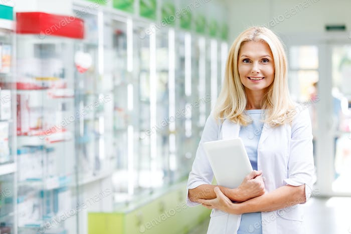 cheerful pharmacist holding digital tablet and smiling at camera in drugstore