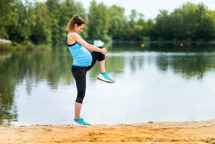 Pregnant woman doing fitness exercises at lakeside, sport during pregnancy