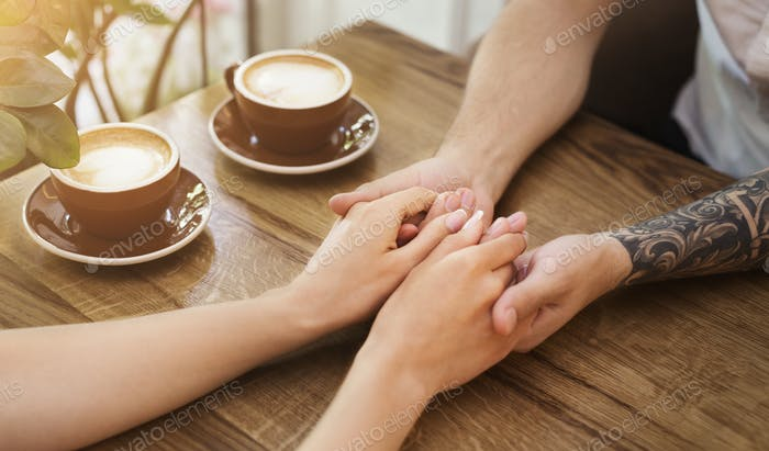 Young couple in love holding hands in cafe