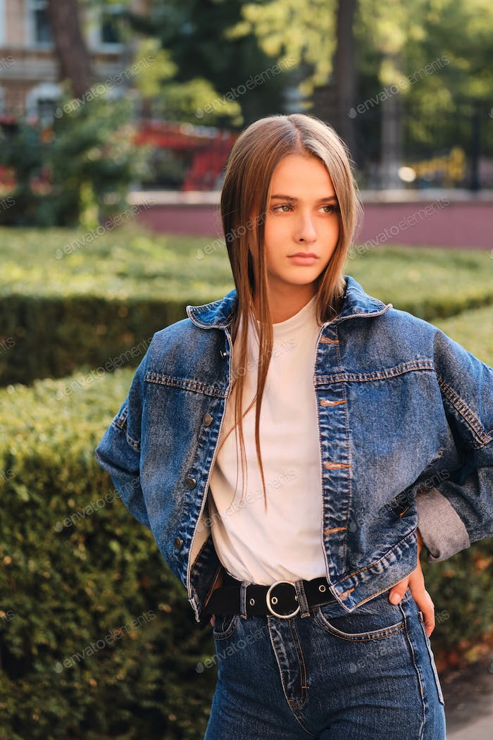Gorgeous serious casual brown haired girl in denim jacket thoughtfully looking away outdoor