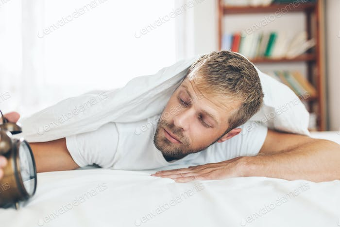 Man finding it difficult to wake up in the morning