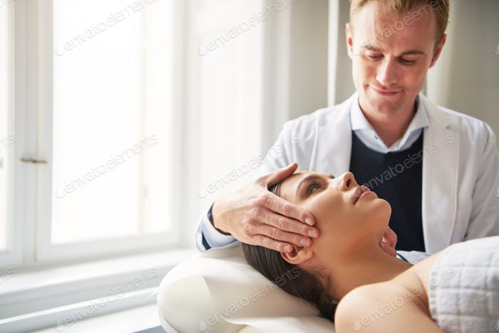 Young beautician holding woman head lying in salon