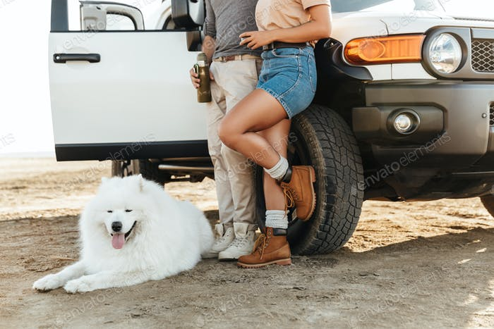 Couple with dog samoyed outdoors at beach near car.