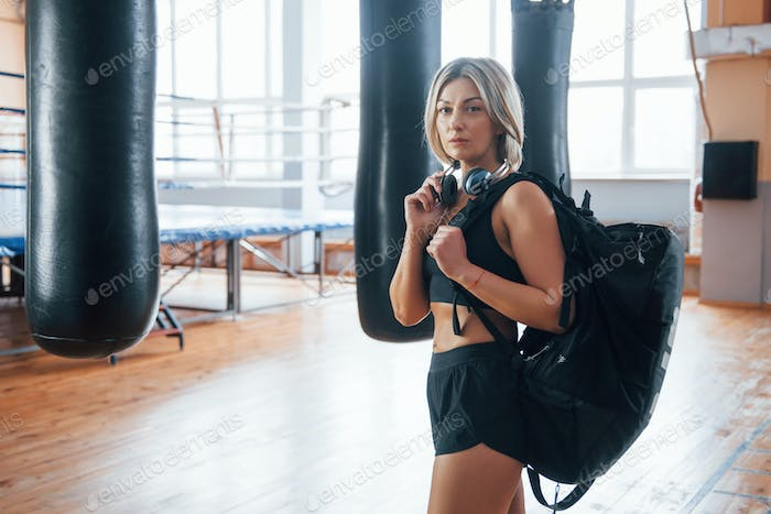 Conception of healthy lifestyle. Adult female with black bag and headphones in the training gym