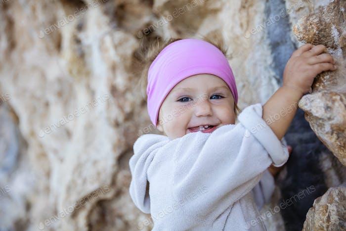 Closeup of little girl gripping cliff