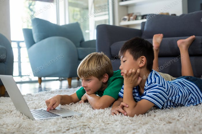 Siblings lying on rug and using laptop in living room