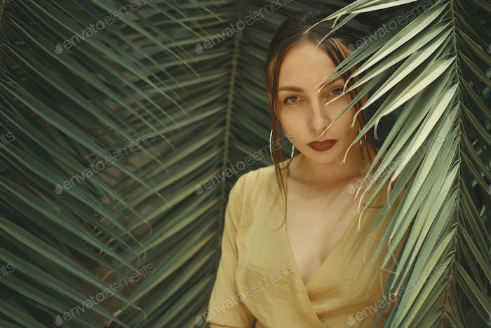 Stunning Woman Posing on Palm Leaves Background