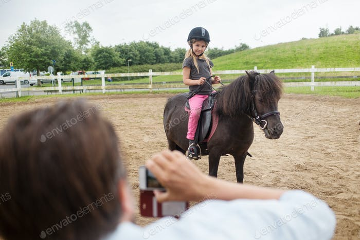 Person photographing girl (4-5) on pony