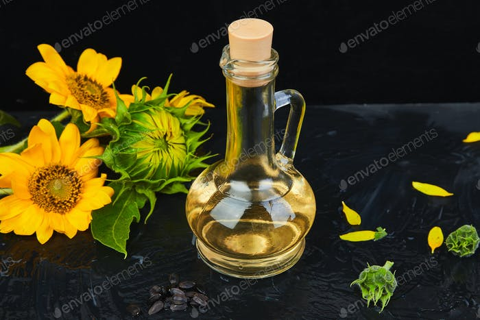Sonnenblumenöl in Glas, Samen und Blumen