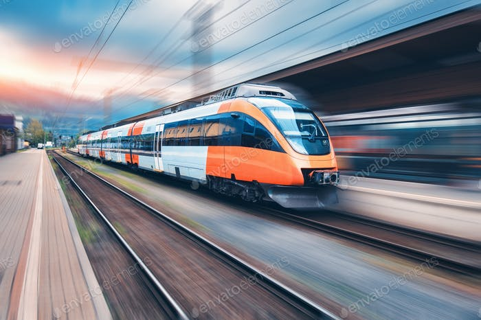 High speed orange train in motion on the railway station