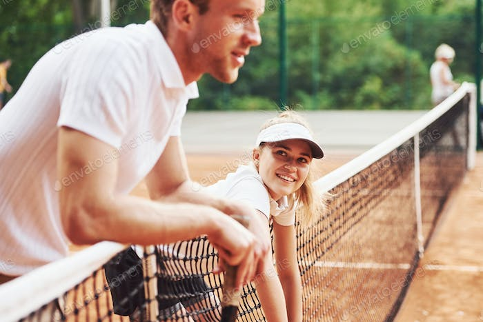 Taking a break by leaning on the net. Two people in sport uniform plays tennis together on the court