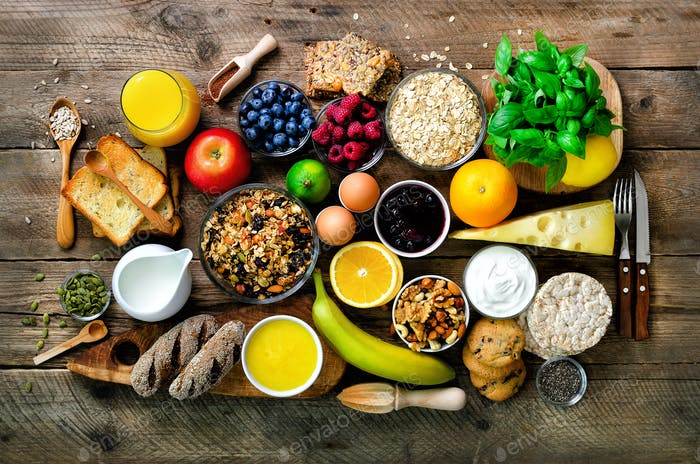 Healthy breakfast ingredients, food frame. Granola, egg, nuts, fruits, berries, toast, milk, yogurt