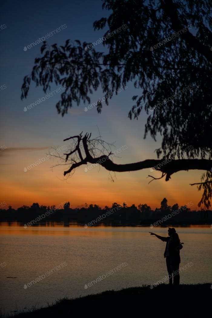 silhouette of young couple standing near the lake