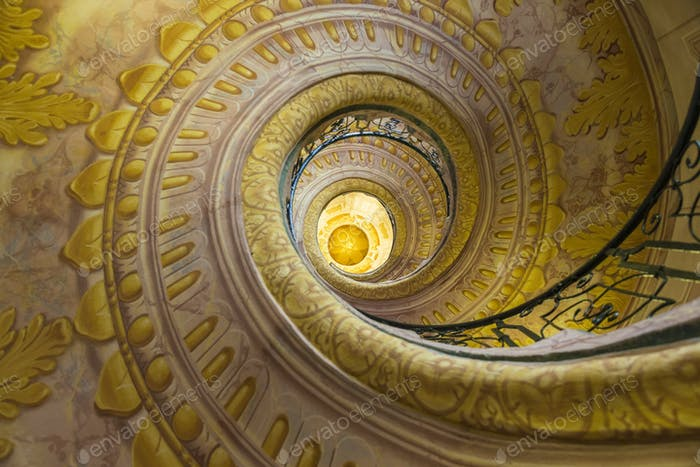 Low angle view of spiral staircase decorated with murals of golden Acanthus flowers and ornamental