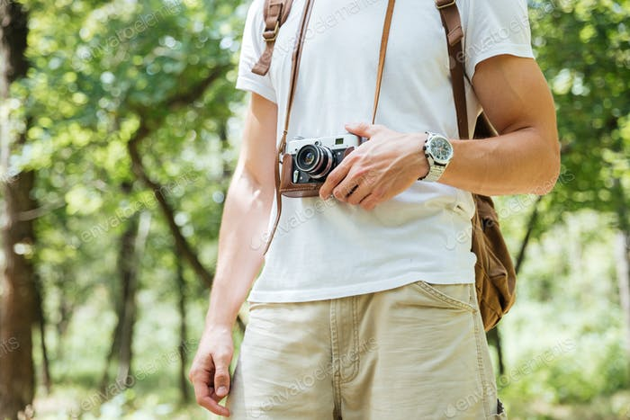 Man with backpack and vintage photo camera in forest