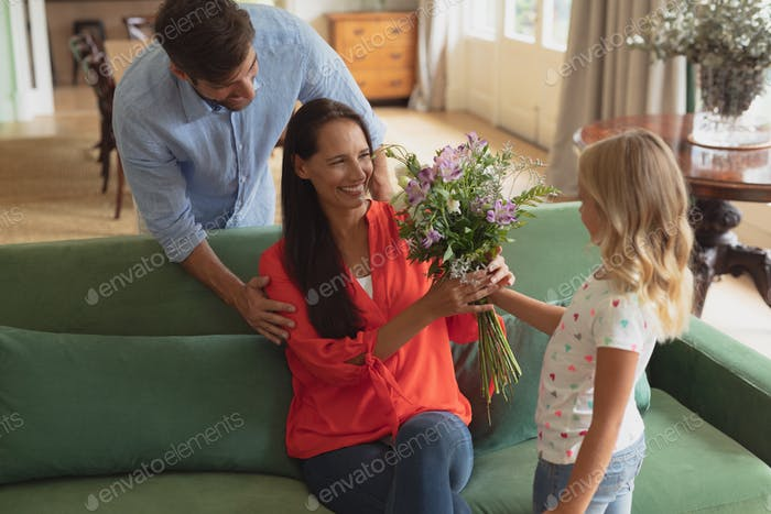 Side view of Caucasian daughter giving bouquet to mother in living room at home
