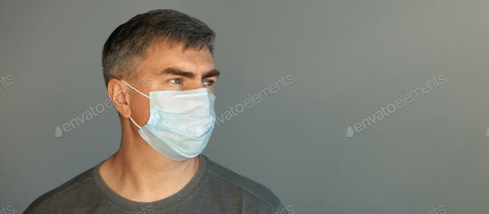 A man in a protective mask and a gray t-shirt