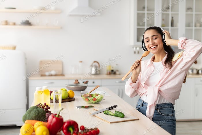 Carefree young woman singing and dancing in kitchen