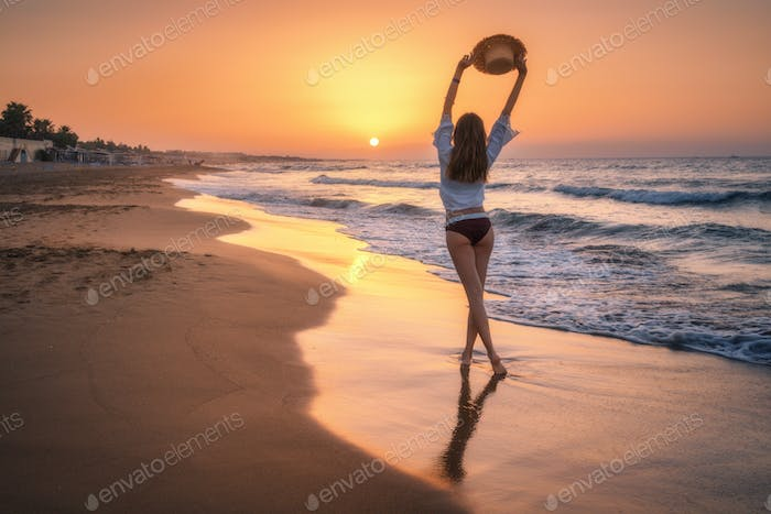 Beautiful woman with straw hat is standing in sea with waves