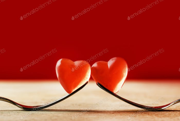 two forks holding red heart