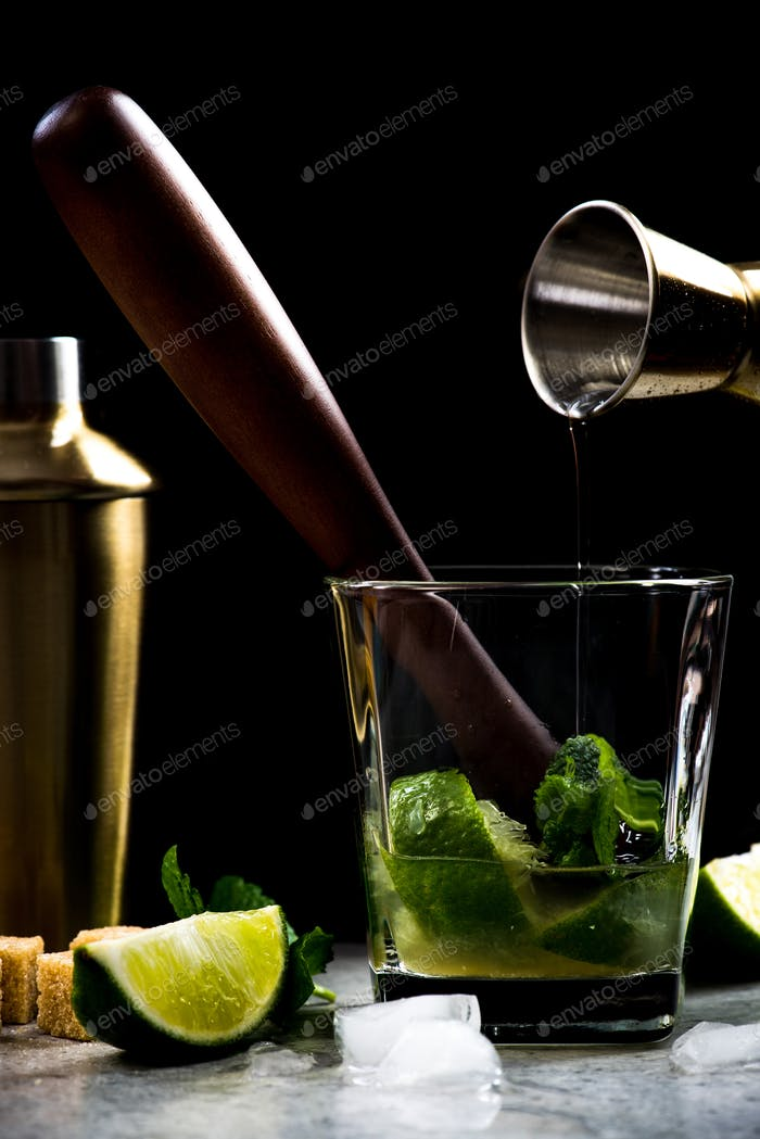 Pouring rum into Mojito cocktail on bar