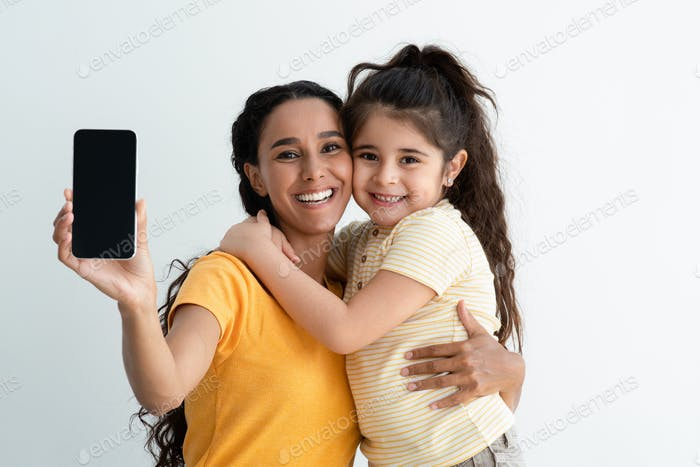 Cheerful Arab Mother And Daughter Demonstrating Smartphone With Black Screen At Camera