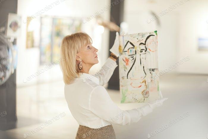Elegante Frau hält Malerei in Kunstgalerie