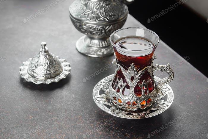 Turkish tea in traditional glass on dark table
