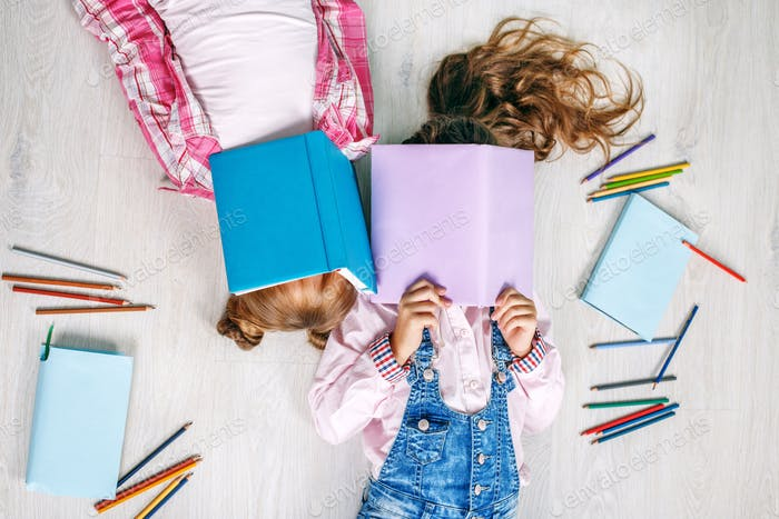 Two little girls with books. Flat lay. The concept of childhood